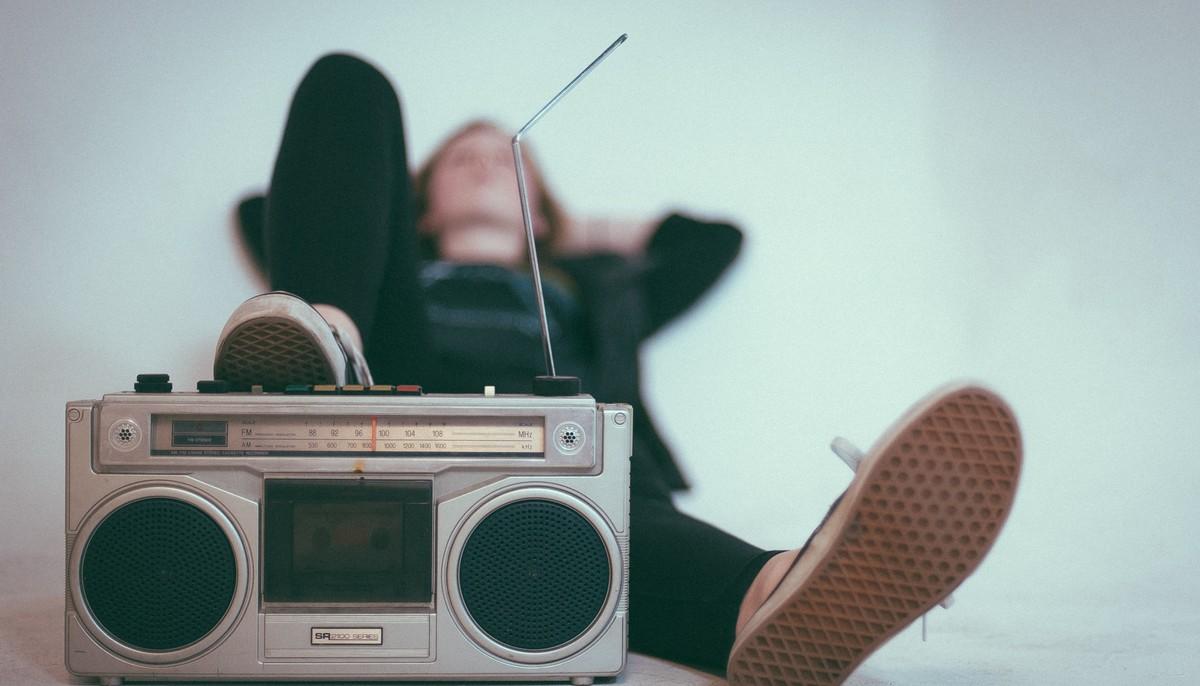 Dívka leží na zemi a poslouchá rozhlas.